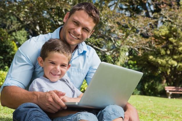 息子と父親はラップトップで笑っている