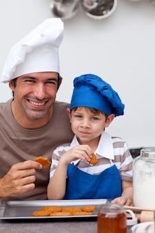Отец и сын едят печенье на кухне