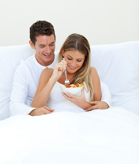 愛情のあるカップルは、ベッドに横たわっている果物を食べる