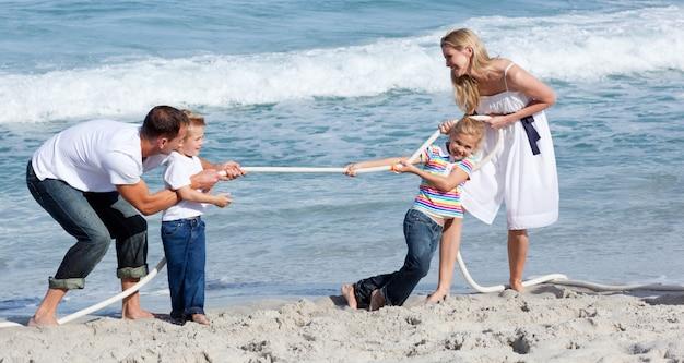 Живая семья играет в перетягивание каната