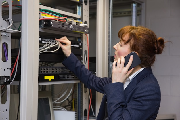 サーバーを修理している間に電話で話すかなりのコンピュータ技術者