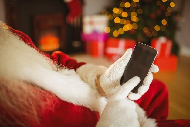 クリスマスのスマートフォンに触れるサンタクロース
