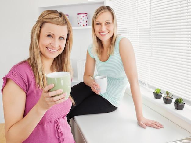 Портрет двух счастливых женщин, проведение чашек кофе у себя дома
