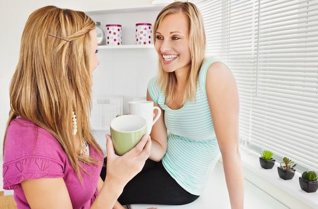 Портрет двух улыбающихся женщин, проведение чашек кофе у себя дома