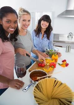 一緒に食事を準備する幸せな友人たちカメラを見て