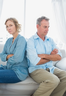 戦いの後に話していないソファに座っている中年のカップル