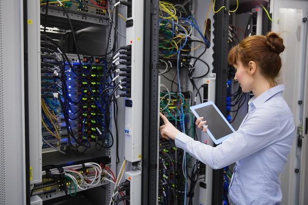 Техник, использующий планшетный пк при анализе сервера