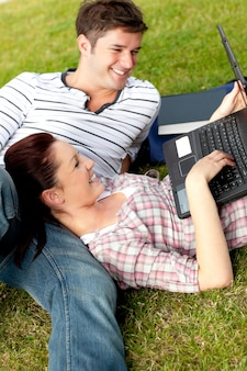 草の上に横たわるラップトップを使用している肯定的な学生のカップル