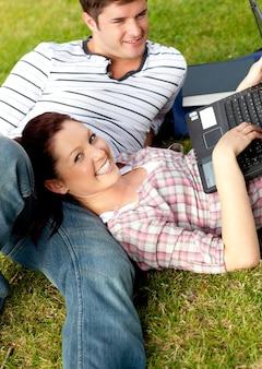 芝生に横たわるラップトップを使用して明るい学生のカップル