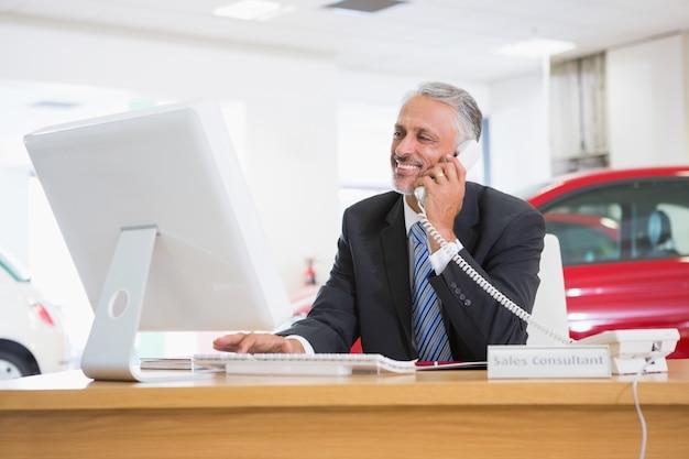 ラップトップを使って笑顔のビジネスマン電話