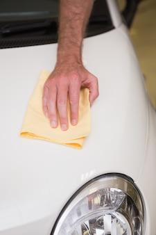 彼の車を掃除する男の近く