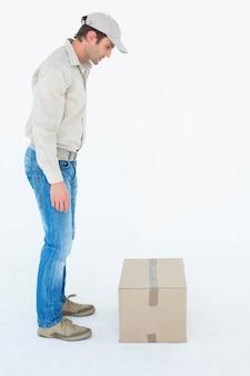 Человек доставки, глядя на картонную коробку