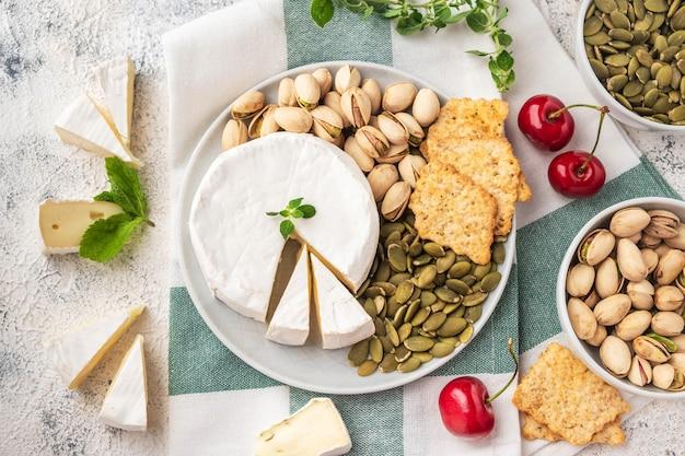 Тарелка с сыром бри, фисташками, тыквенными семечками, вишней.
