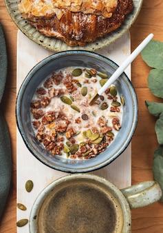 木製のテーブルで朝食:グラノーラ、クロワッサン、コーヒー。