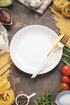 Пустая тарелка со столовыми приборами в рамке из макарон, овощей и ингредиентов для приготовления пищи