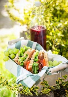 Хамон и овощные бутерброды в корзине, виноград и ягодный сок, пикник на свежем воздухе, крупный план
