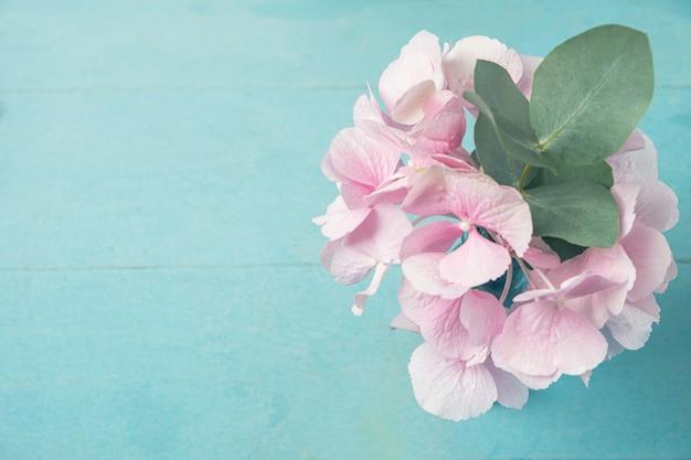 青い木製のテーブルの上に花瓶にユーカリの枝とピンクのアジサイの花を残します