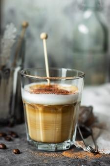 テーブルの上のガラスカップでカプチーノコーヒー