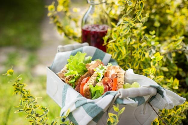 Бутерброды с ветчиной и овощами в корзине