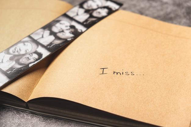 幸せなカップルと手書きの碑文の写真でノートブックを開く