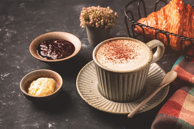 テーブル、朝食のコンセプト、トップビューでクロワッサンとカプチーノコーヒー