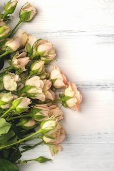 Букет из маленьких светло-розовых роз на белом деревянном столе, копия пространства, крупный план