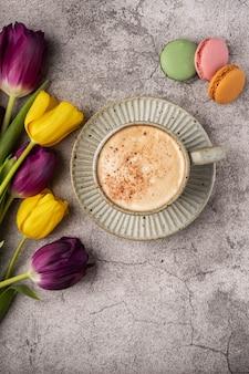 Фиолетовые и желтые тюльпаны, чашка с кофе и миндальное печенье на сером бетонном столе, копией пространства