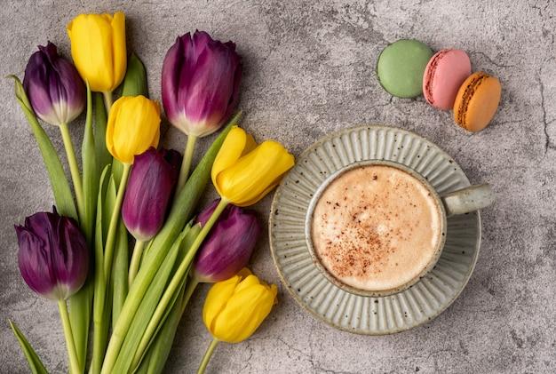 Фиолетовые и желтые тюльпаны, чашка с кофе и миндальное печенье на сером бетонном столе