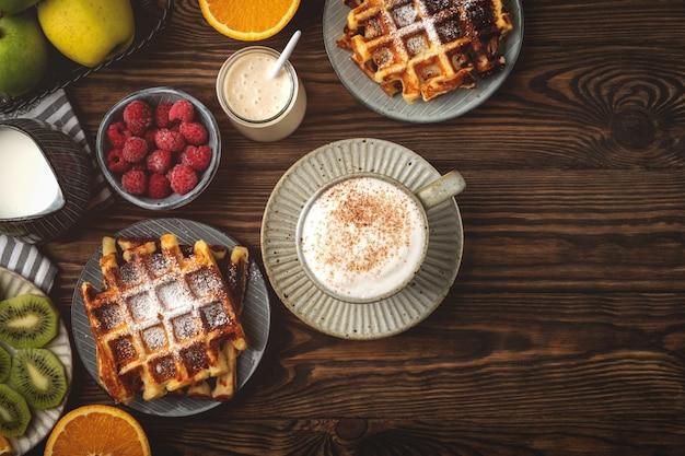 ベルギーワッフル、コーヒー、ヨーグルト、フルーツ、木製の背景、朝食コンセプトのベリー。