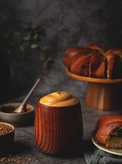 木製カップのダルゴナコーヒーとスタンドのケーキ。ふわふわのホイップコーヒー。トレンド韓国ドリンク。
