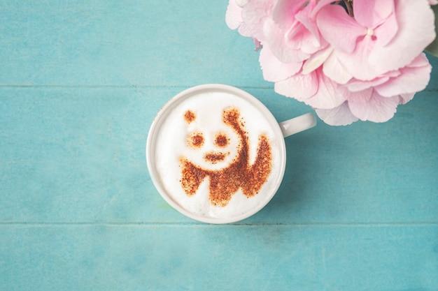 青い木製の表面の泡にパンダパターンとコーヒーの白いカップ、