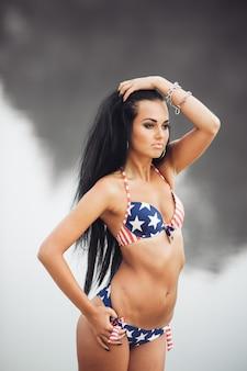 Девушка на пляже с американским флагом