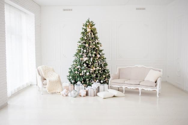 古典的なクリスマス新年はインテリアルーム新年ツリーを装飾されています。金の装飾とクリスマスツリー。モダンな白いクラシックスタイルのインテリアデザイン