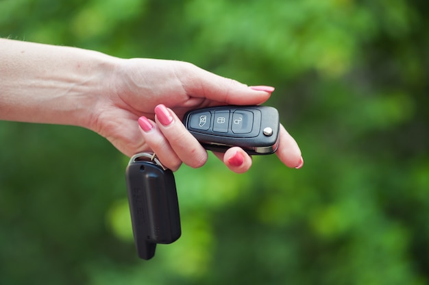Ключ от машины в женской руке. продавец автомобилей. открытие и сигнализация