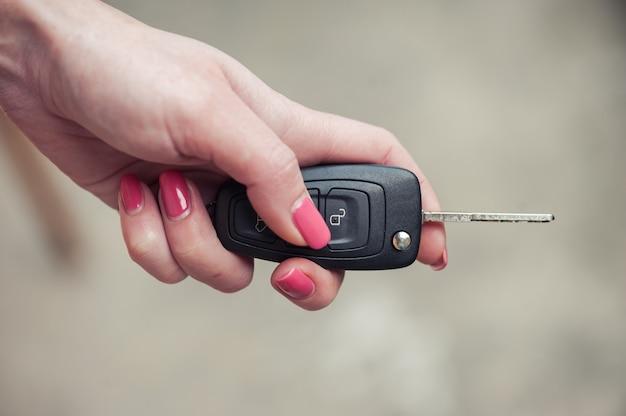 Ключ от машины в женской руке. продавец автомобилей. открытие и сигнализация. авто продажа и подарок