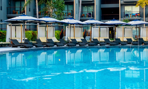 ホテルリゾートの屋外スイミングプールの周りの傘と椅子のソファ