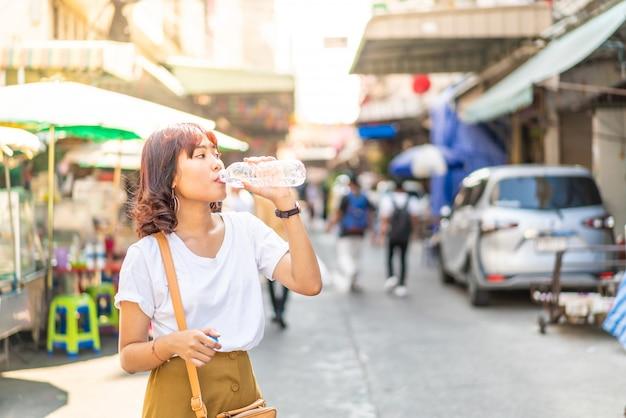 リフレッシュのために飲む水のボトルを保持しているアジアの女性旅行者