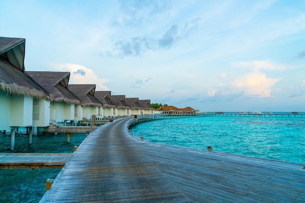 Красивый тропический закат над островом мальдивы с бунгало на воде в курортном отеле