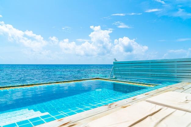 モルディブの海の背景付きのスイミングプール
