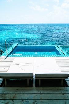 ベッドプールとモルディブの海の背景を持つスイミングプール