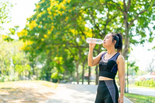 Азиатская женщина питьевой воды в спортивной одежде