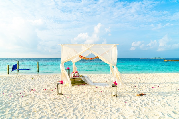 熱帯のモルディブリゾートと海とビーチでの結婚式のアーチ