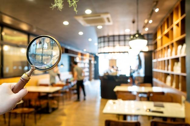 抽象的なぼかしカフェレストランの背景を持つカフェレストラン付きの虫眼鏡