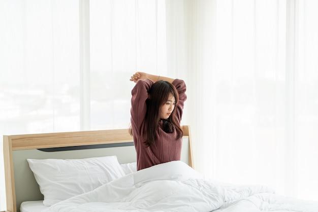 ベッドの上の美しいアジアの女性と朝目を覚ます