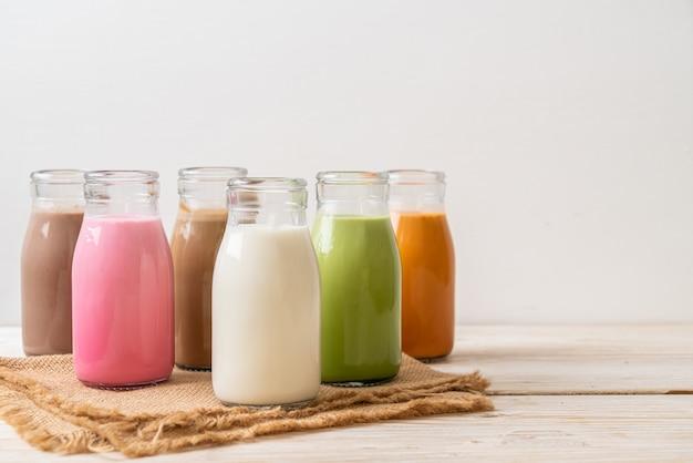 飲料のコレクションです。タイの牛乳茶、抹茶抹茶ラテ、コーヒー、チョコレートミルク、ピンクミルク、木のテーブルにボトルに入った新鮮な牛乳