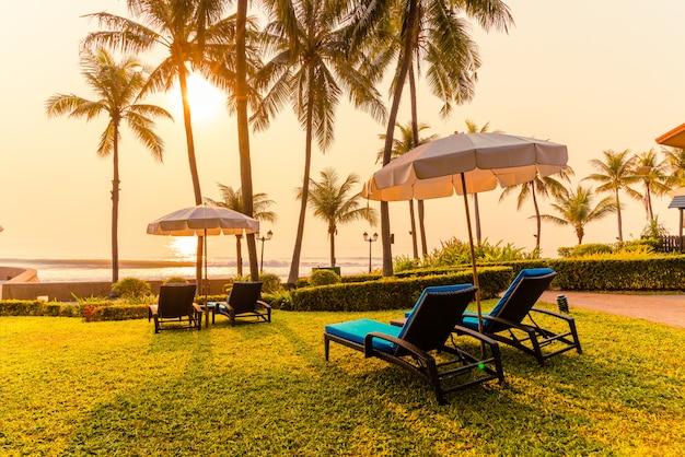 ホテル、リゾート、休暇、休日のコンサートで美しい傘とスイミングプールの周りの椅子