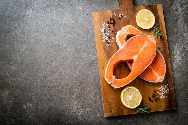 Свежий сырой стейк из филе лосося с ингредиентом на борту