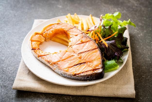 Стейк из лосося на гриле с овощами и картофелем фри на тарелке