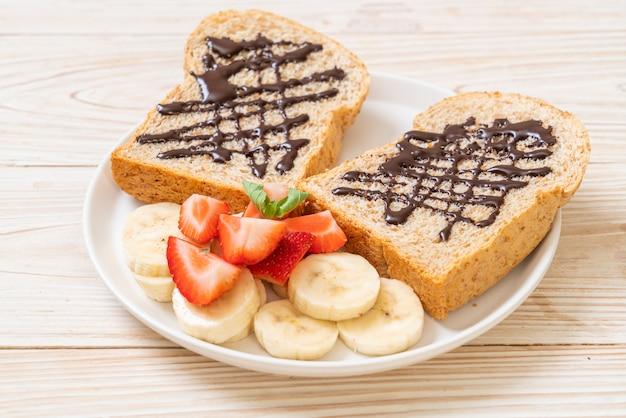 朝食用の新鮮なバナナ、イチゴ、チョコレートでトーストした全粒小麦のパン
