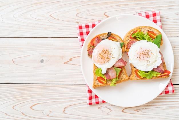 Хлеб из цельной пшеницы поджаренный с овощами, беконом и яйцом или яйцом бенедикт на завтрак